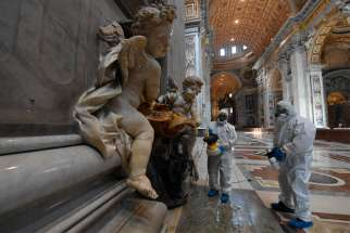 Vatican workers in protective gear sanitize various surfaces inside St. Peter's Basilica at the Vatican May 15, 2020, ahead of the resumption of Masses during the COVID-19 pandemic.