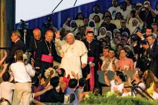 Pope John Paul II waves to the vast crowd that attended the vigil at Toronto's Downsview Park during World Youth Day 2002. More than 800,000 attended the week-long event.