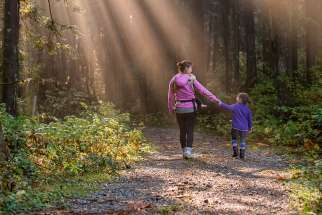 A mother and daughter walking in a forest in Maple Ridge, Canada.