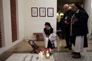 Nuns and others stand next to a photograph of Bishop Pierre Claverie at his grave in St. Mary's Cathedral, where a vigil was held, in Oran, Algeria, Dec. 7. The vigil was to prepare for the Dec. 8 beatification of Bishop Claverie and a group of 18 others, who were martyred in the course of the Algerian civil war.