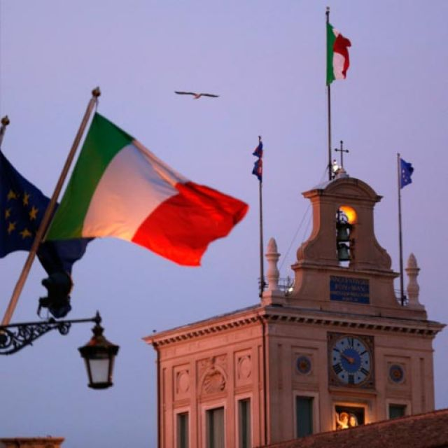 Italian flags blow in the breeze outside the presidential palace in Rome Dec. 22. When Italians go to the polls Feb. 24, the pope and other church officials will be watching closely.