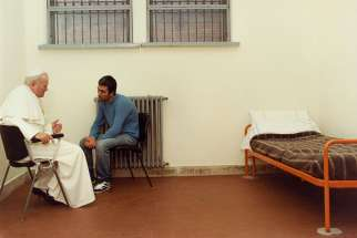 St. John Paul II sits with his would-be assassin, Mehmet Ali Agca, in Rome's Rebibbia prison in this 1983 photo. Mehmet Ali Agca laid a bunch of white roses at St. John Paul II's tomb exactly 31 years after the late Pope forgave him for shooting and trying to assassinate him.