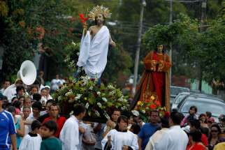 Worshippers carry a statue of the risen Christ during an Easter procession in Escazu, Costa Rica, April 8, 2012.