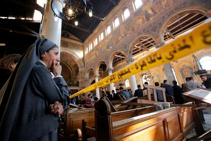 A nun cries as she stands inside St. Mark's Coptic Orthodox Cathedral Dec. 11, 2016 after an explosion inside the cathedral complex in Cairo. A bomb ripped through the complex, killing at least 25 people and wounding dozens, mostly women and children.