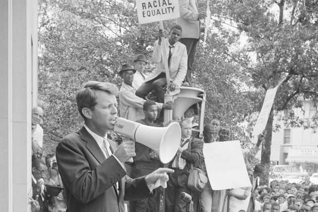 Attorney General Robert F. Kennedy speaking to a crowd of African Americans and whites through a megaphone outside the Justice Department Jun. 14, 1963.