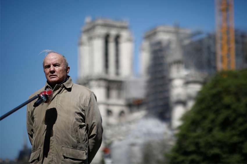 French Army Gen. Jean-Louis Georgelin, in charge of the Notre Dame Cathedral reconstruction, stays at a distance to answer journalists' questions in Paris April 14, 2020, during the coronavirus pandemic. French President Emmanuel Macron has reiterated a pledge to restore the historic cathedral by 2024.