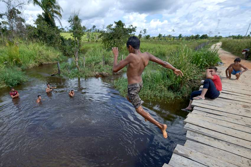 Children jump from a rickety bridge into a river near Anapu, in Brazil's northern Para state. This area was forest land until recent decades, when the expansion of the agrarian frontier led to the steady destruction of this part of the Amazon's rain forest.