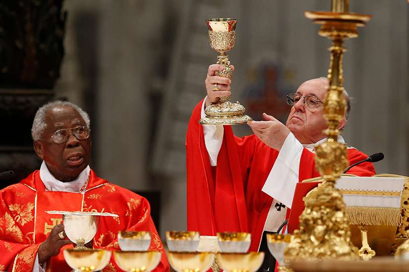 "Pope Francis elevates the Eucharist as he celebrates Mass marking the feast of Pentecost in St. Peter's Basilica at the Vatican May 20. Alson pictured is Nigerian Cardinal Francis Arinze. The pope at his ""Regina Coeli"" announced that he will create 14 new cardinals June 29."