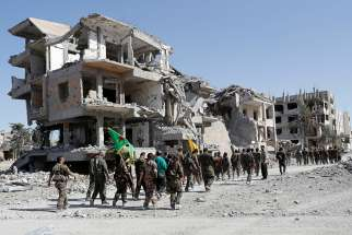 Fighters with the Syrian Democratic Forces march past destroyed buildings in 2017 in Raqqa.