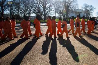 Activists dressed in orange jumpsuits representing detainees in the U.S.-run detention centre at Guantanamo Bay, Cuba, rally in front of the White House Jan. 11 asking President Barack Obama to close the facility and release or charge the dozens of men being held there.