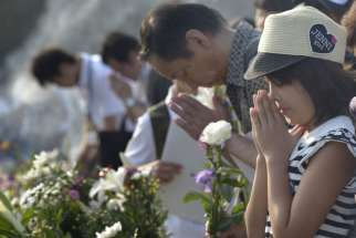 People pray at a memorial in Hiroshima, Japan, Aug. 6, to commemorate the victims of the atomic bombing of the city by the United States in 1945. Delegation members from the World Council of Churches, in Hiroshima for the commemoration, said they would return home to build a movement to rid the world of nuclear weapons.
