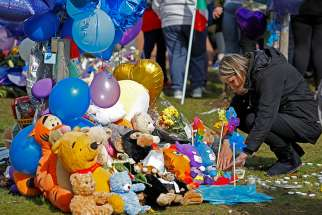 A woman looks at flowers, candles and toys left as a memorial to Alfie Evans in Liverpool, England, April 28. The 23-month-year-old died April 28 from complications of a degenerative brain condition.