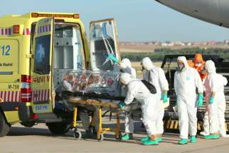 Health workers put Ebola patient, Father Miguel Pajares of Spain, into an ambulance Aug. 7 at a military air base in Madrid, after he was repatriated from Liberia for treatment. Ghana's bishops have urged the government to be extra vigilant in screening people who enter the country by sea for signs of Ebola.