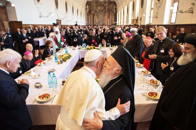Pope Francis is greeted by Ecumenical Patriarch Bartholomew of Constantinople during an interfaith peace gathering Sept. 20 at the Basilica of St. Francis in Assisi, Italy. During the gathering Pope Francis invited refugees to lunch with him.