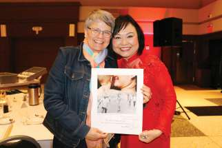 Kim Phuc gives a signed poster to audience member Laurena Hensel that shows the famous photograph during the Focus on Life Gala.