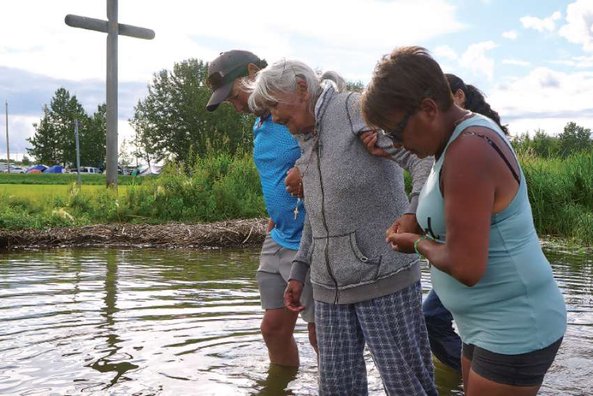 Mary Agnes Herman is helped out of Lac Ste. Anne after walking 429 kilometres to the pilgrimage site.
