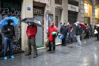 People wait in line for free food outside the Church of Santa Anna in Barcelona, Spain, April 21, 2020, during the COVID-19 pandemic. The parish publishes a daily tally of meals and hygiene equipment handed out to needy recipients, as well as a blog with advice for surviving the crisis.