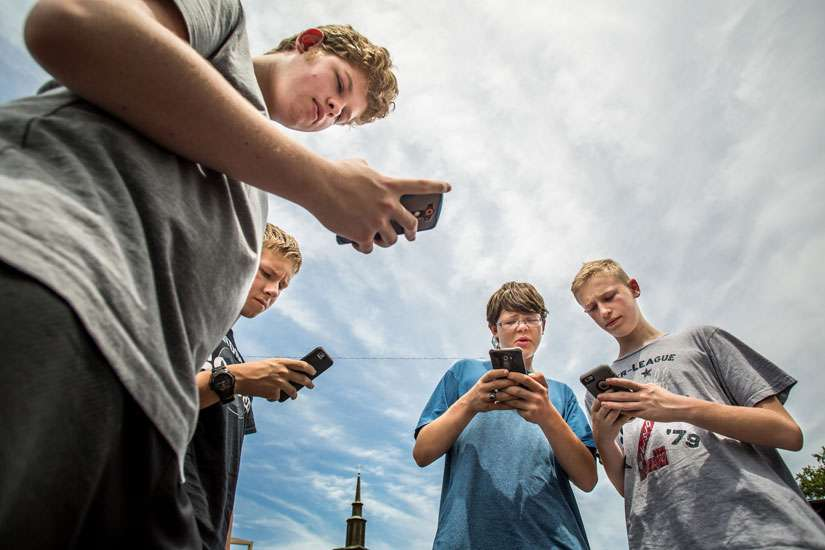 Alec Richardson, Brennan Moore, Adam Salman and Blake Koelz hunt Pokemon stops July 14 around the grounds of Assumption Church in St. Louis.