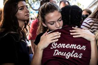 Students from Marjory Stoneman Douglas High School attend a memorial Feb. 15, 2018, following a school shooting in Parkland, Fla. Feb. 14 marks the first anniversary of the shooting that killed 14 students and three staff members at the school.