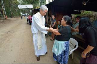 Jesuit Father Jose Antonio Pacheco greets gold mine protesters during Mass along a road in La Puya, Guatemala, Dec. 7. Mining has divided the church in Guatemala, with environmentalist Bishop Alvaro Ramazzini of Huehuetenango receiving death threats.