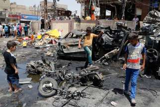 "Boys look at the site of a car bomb attack in Baghdad, Iraq, Aug. 1. The Vatican called on Muslim leaders to condemn the ""barbarity"" and ""unspeakable criminal acts"" of Islamic State militants in Iraq."