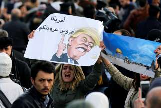 "Protesters near the U.S. embassy in Amman, Jordan, hold a lampoon of President Donald Trump Dec. 7. The cartoon reads, ""America is the Arab leader."""