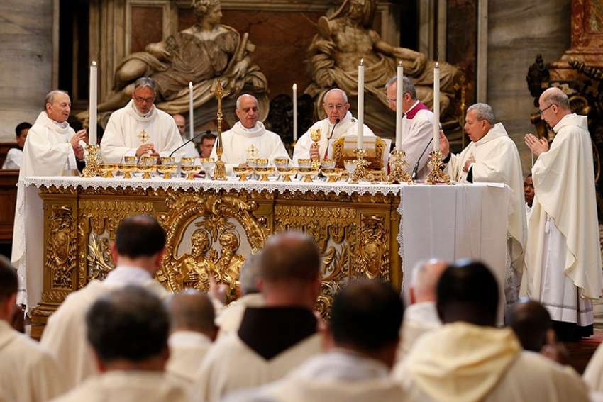 Pope Francis holds a chalice while concelebrating Mass with hundreds of priests who are missionaries of mercy in St. Peter's Basilica at the Vatican April 10. The pope has continued the mandate of the missionaries of mercy.