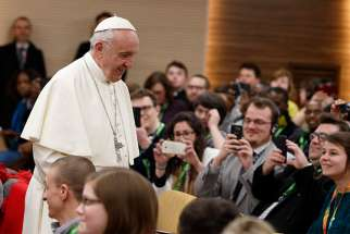 Pope Francis prepares to take a photo with young people at a presynod gathering of youth delegates in Rome March 19. The Vatican has released the working document for the October Synod of Bishops on young people, the faith and vocational discernment.