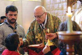 Melkite Archbishop Issam Darwich of Zahle, Lebanon, distributes Communion to Syrian refugee families at the Melkite Catholic archeparchy in Lebanon's Bekaa Valley in this 2017 file photo.