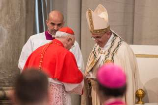 Pope Francis presents a document officially proclaiming the 2015-2016 extraordinary Holy Year of Mercy to a cardinal in St. Peter's Basilica at the Vatican April 11. The pope handed copies of the document to the archpriests of the major basilicas of Rome and to Vatican officials representing Catholics around the world.