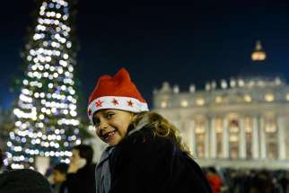 Carla Maria Valenzi, 6, wears a Christmas hat in St. Peter's Square after Pope Francis' Christmas Eve Mass at the Vatican Dec. 24
