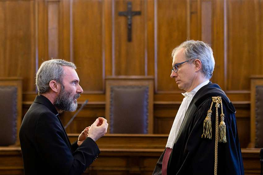 Msgr. Carlo Alberto Capella, left, a former Vatican diplomat who served in Washington, talks to his lawyer during his sentencing in a Vatican court June 23. Msgr. Capella was found guilty of possessing and distributing child pornography and sentenced to five years in a Vatican prison and fined 5,000 Euro.