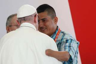 Pope Francis embraces man who spoke during a national reconciliation prayer meeting at Las Malocas Park in Villavicencio, Colombia, Sept. 8.