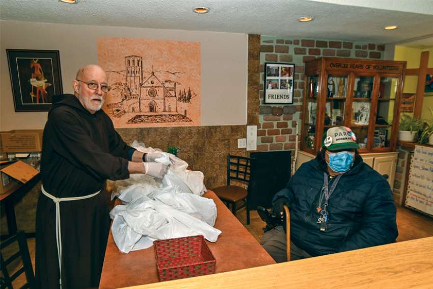 Franciscan Br. John Corriveau, the retired Bishop of Nelson, B.C., hands a takeout meal to Chico, one of the regulars at St. Francis Table, in the early days of the COVID-19 pandemic. St. Francis Table is experiencing a volunteer shortage during the crisis.