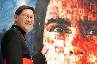Philippine Cardinal Luis Antonio Tagle of Manila, president of Caritas Internationalis, points to a photo of his maternal grandfather, who emigrated from China to the Philippines.