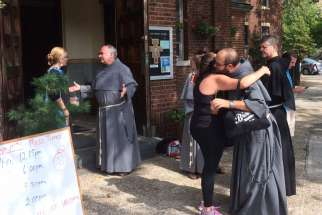 Conventual Franciscan friars greet the residents of the Greenpoint/Williamsburg section of Brooklyn, N.Y., Aug. 23, 2015, shortly after they opened their San Damiano Mission in the neighborhood, which had been the Holy Family (Slovak) Church.