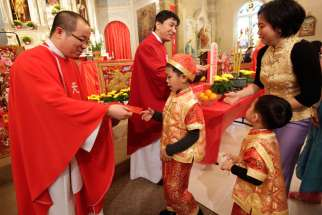 Fathers CheLong Bai and RunBao Zhang pass out red envelopes following Mass at St. Therese Chinese Church in Chicago's Chinatown at the start of the Chinese lunar new year in 2014.