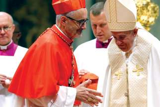 Cardinal Michael Czerny has a few words with Pope Francis after receiving his red biretta in St. Peter's Basilica at the Vatican on Oct. 5.