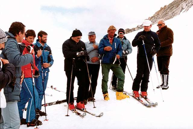 Pope John Paul II, in a black ski jacket and hat, prays with a group of skiers before heading down a slope in Italy in 1984.