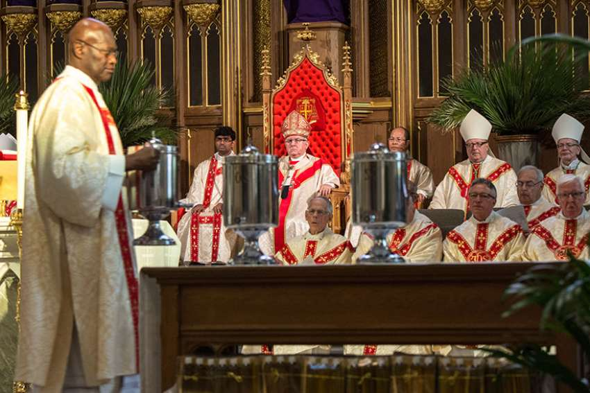 The chrism oil to be used for the next year in baptisms, confirmations and ordinations is brought to the altar during the annual Chrism Mass April 11 at St. Michael's Cathedral.