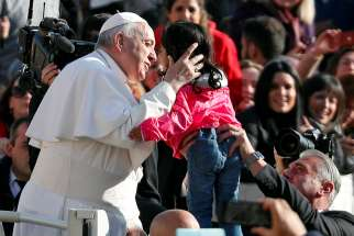 Pope Francis embraces a child as he arrives to lead the weekly general audience in St. Peter's Square at the Vatican Nov. 14.