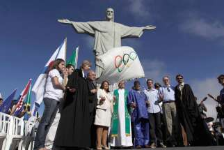 "Rio de Janeiro's Mayor Eduardo Paes, in untucked dress shirt; Brazilian Olympic Committee President Carlos Arthur Nuzman, in khaki pants; and leaders of different religions pray next to the Olympic Flag in front of ""Christ the Redeemer"" statue during a blessing ceremony in Rio de Janeiro on Aug. 19, 2012"