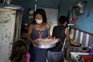 Vanderlecia Ortega dos Santos is seen with her family in their kitchen in Manaus, Brazil, May 7, 2020. Santos is a nurse who has volunteered to provide the only frontline care protecting her indigenous community of 700 families during the COVID-19 pandemic.