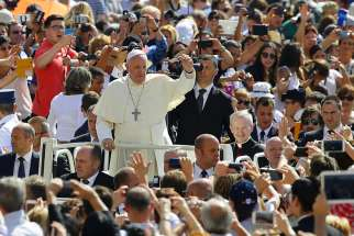 Pope Francis waves as he arrives to lead his general audience in St. Peter's Square at the Vatican June 17.