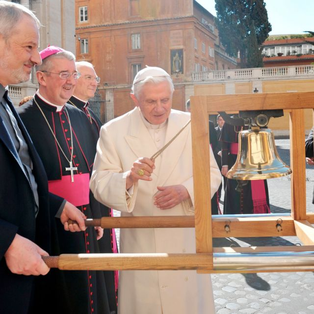 Pope Benedict XVI rings the International Eucharistic Congress Bell before his general audience at the Vatican March 14. At left are Father Kevin Doran, secretary general of the International Eucharistic Congress, and Archbishop Diarmuid Martin of Dublin , president of the congress.