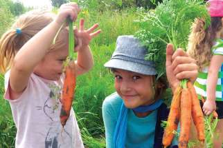 Olivia Stocking-Lopez, left, and her cousin Amy Stocking harvest some of the organic vegetables to be eaten during the Food Family Faith weekend retreat in Sharon, Ont.