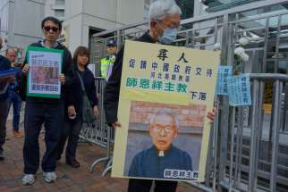 Cardinal Joseph Zen Ze-kiun, retired bishop of Hong Kong, wears a protective mask and holds a picture of Bishop Cosmas Shi Enxiang of Yixian Feb. 14 outside a government building in Hong Kong. Bishop Shi is said to have died under detention.