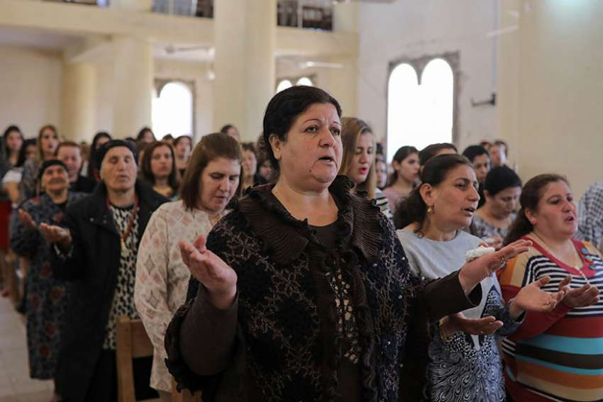 Worshippers pray during Easter Mass April 16 in St. George Chaldean Catholic church in Tel Esqof, Iraq. The church was damaged by Islamic State militants.
