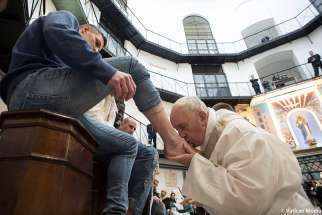 Pope Francis kisses the foot of an inmate during Holy Thursday Mass at Regina Coeli prison in Rome in this March 29, 2018, file photo. The pope will wash the feet of prisoners on Holy Thursday at Velletri Correctional Facility, about 36 miles south of Rome.