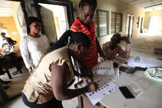 An electoral agent in Lagos, Nigeria, inspects the temporary voter card of a woman Feb. 10.